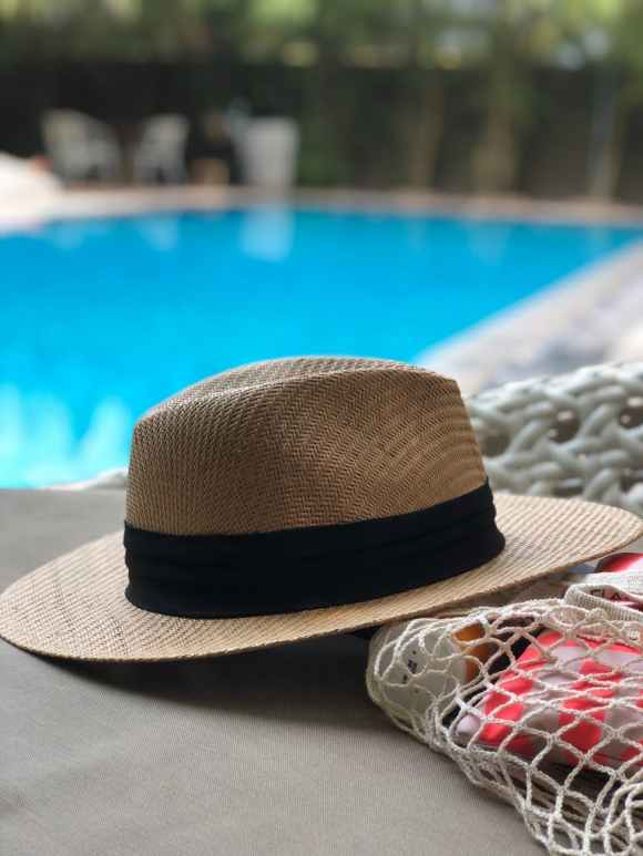 beige and black hat near swimming pool